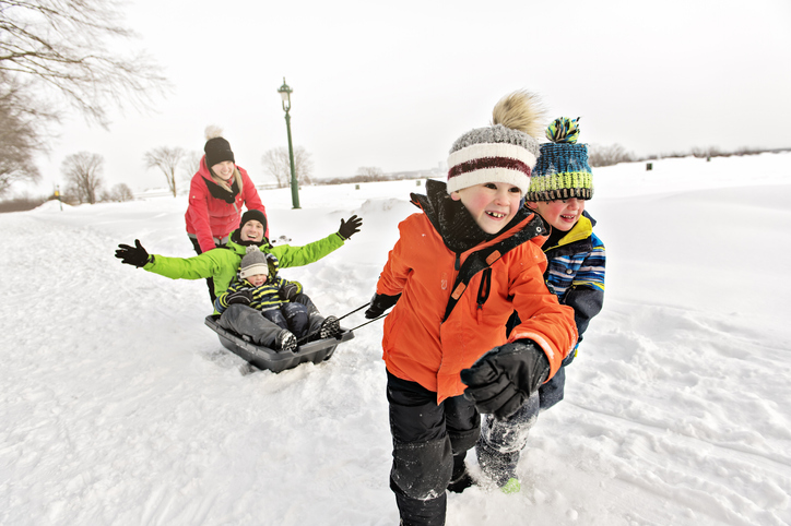 A family with young kids sledding on fresh snow